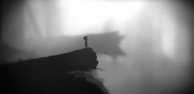 Limbo protagonist stands on the edge of a fallen tree, overlooking a fog-covered valley